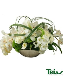 Lush arrangement of white roses, mini callas, orchids and lush greens.