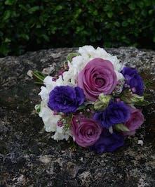 Unique junior bouquet with touches of purple.