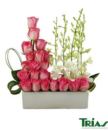 Elongated white ceramic vase with pink roses and white dendrobium orchids.