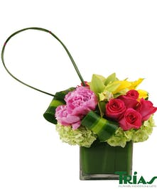 Clustered arrangement with beautiful pink peonies, pink roses, and yellow mini callas.